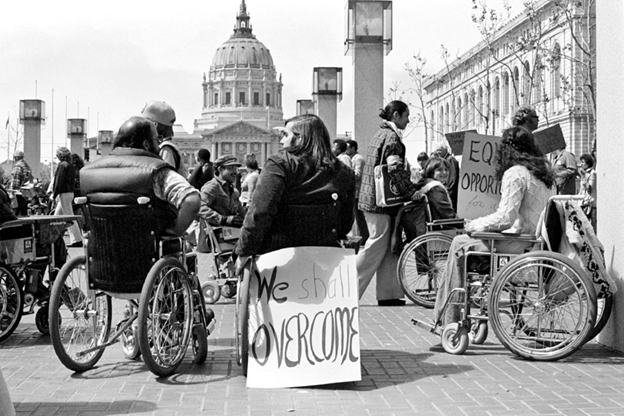 A crowd in wheelchairs with protest signs in front of the capital building