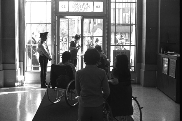 Several people in wheelchairs inside a large glass door, with security next to the door
