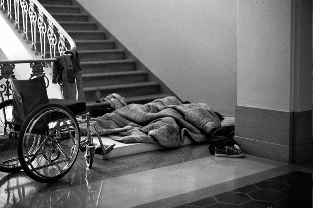 Two people sleeping on a thin foam mattress at the bottom of a large staircase, next to a wheelchair